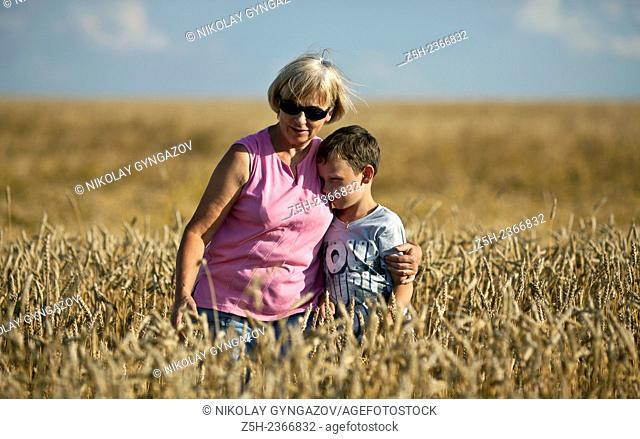 Wheat fields of the Belgorod region. Grandmother with grandson in a wheat field
