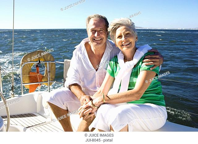 Mature couple sitting on deck of yacht out at sea, man with arm around woman, smiling, portrait