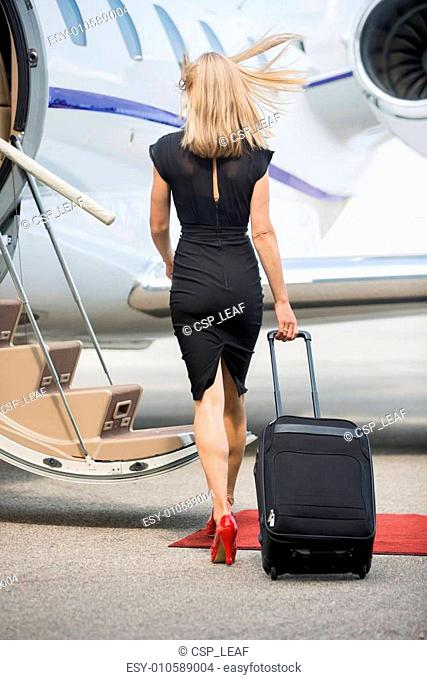 Rich Woman With Luggage Walking Towards Private Jet