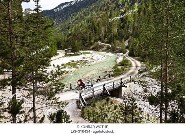 Cyclists passing bridge, Isar Cycle Route, Hinterau Valley, Karwendel range, Tyrol, Austria