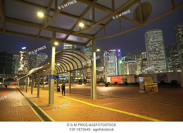 one woman walking a ferry terminal with Hong Kong night skyline in the background