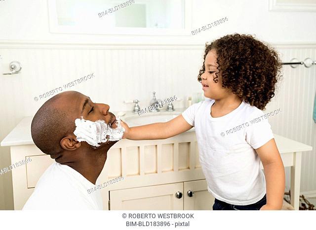 Boy helping father shave in bathroom