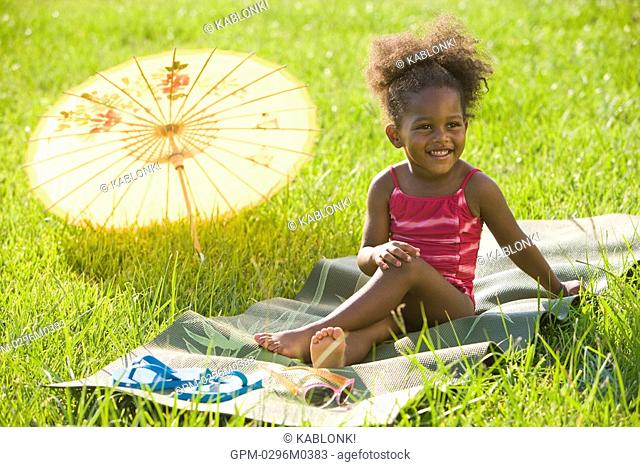 Portrait of young African American girl in bathing suit relaxing in grass
