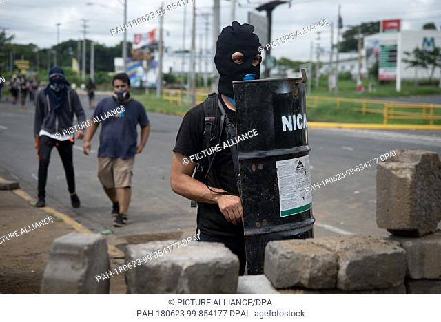 23 June 2018, Nicaragua, Managua: Hooded students stand in the university with a self-made shield. Paramilitaries stormed the National Autonomous Universities...