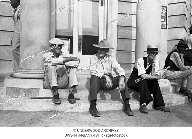 Crowley, Louisiana: October, 1938 Men sitting on the steps of a bank during the National Rice Festival