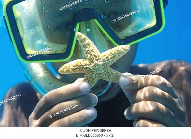 Hispanic boy in goggles holding starfish