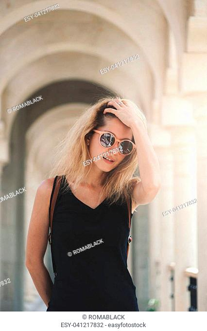 Young tourist woman in black dress and sunglasses standing at the arch background