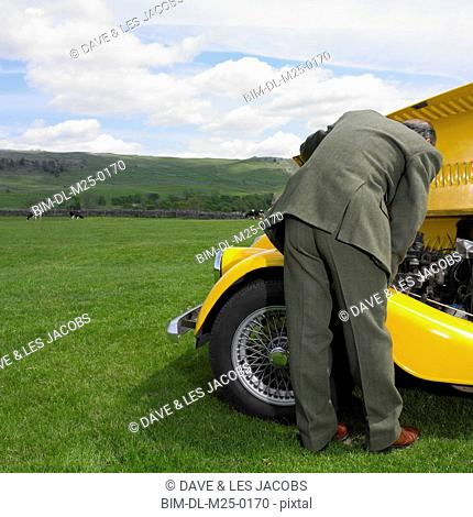 Man in suit looking under hood of old car in countryside
