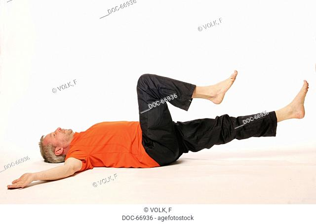older man lying on the floor on his backside - both arms on the side of his head - on leg is streched and the other one is bented in direction to the belly -...