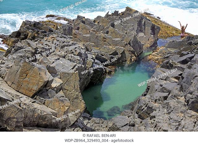 Woman enjoys swimming in Fairy Pools in Noosa Heads, Sunshine Coast, Queensland