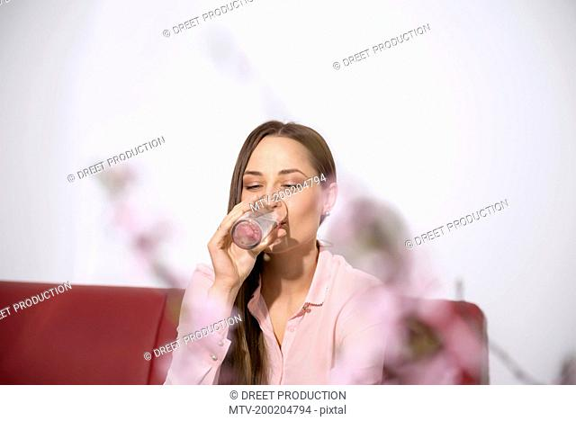 Young woman sofa sitting drinking water