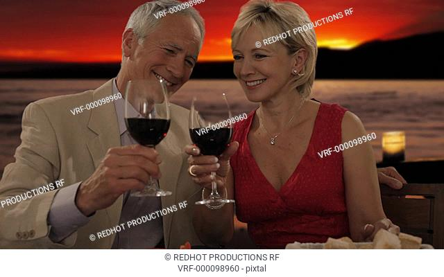 senior couple at dinner in sunset toasting camera