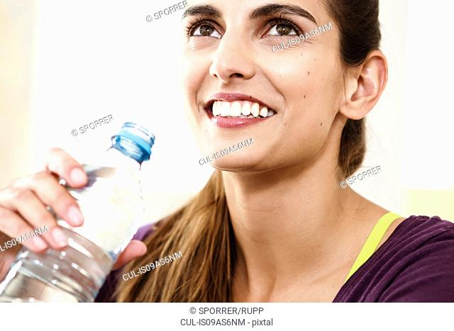 Close up portrait of young woman taking an exercise break drinking water
