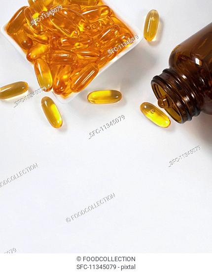 Fish oil capsules in a dish and a bottle