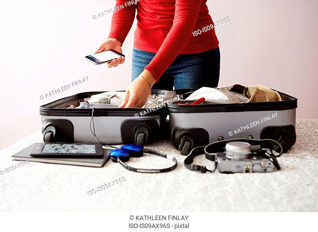 Woman packing suitcase, holding smartphone, mid section