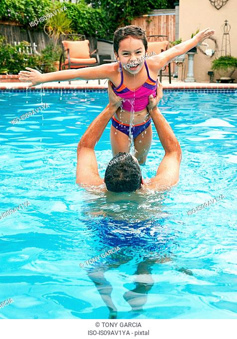 Father in swimming pool lifting up daughter, arms open looking at camera smiling