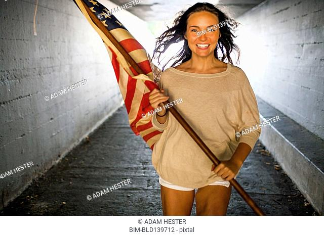 Caucasian woman carrying American flag in tunnel