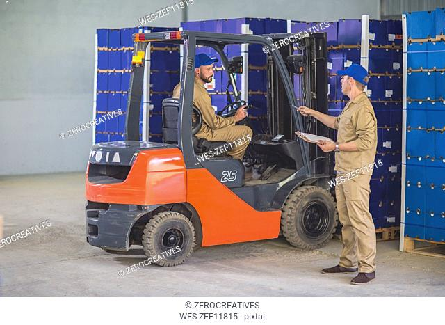 Worker stocking load with forklift