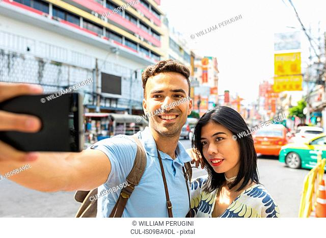 Young tourist couple taking smartphone selfie on street, Bangkok, Thailand