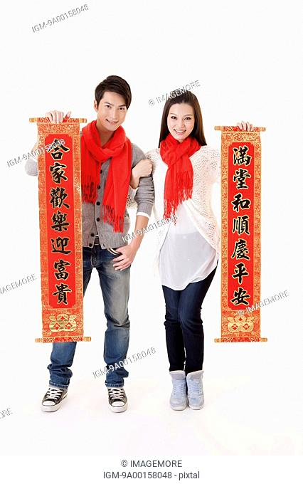Young couple holding Chinese couplet and smiling at the camera together