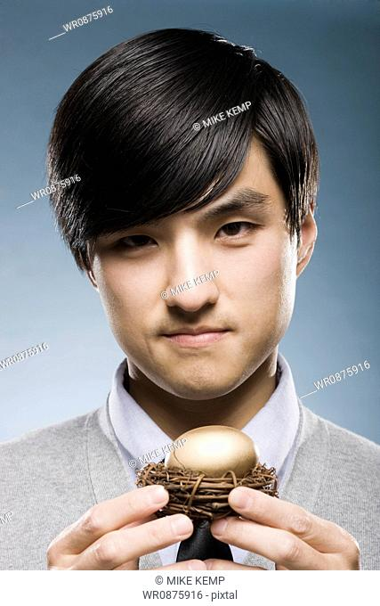 man holding a golden egg in a nest