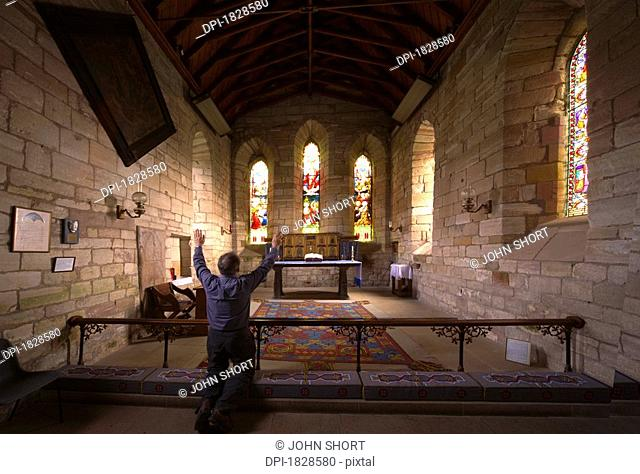 Man praying in chapel, Holy Island, Bewick, England