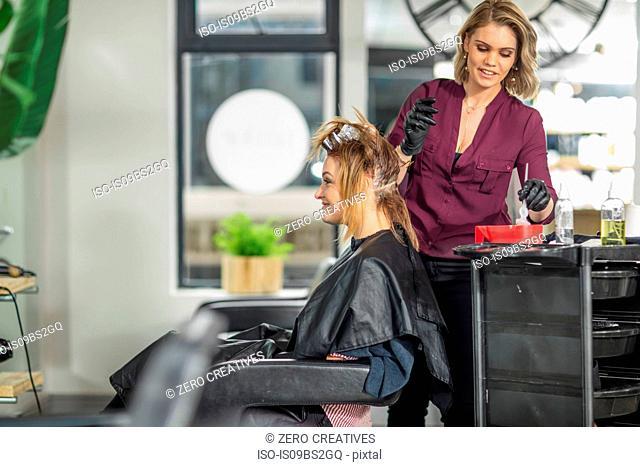Hairdresser colouring customer's hair in salon