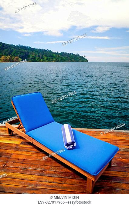 Outdoor reclining seat on deck next to lake. Matching blue and white towel rolled up on top