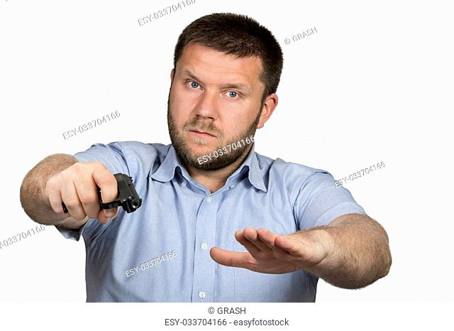 Man with a beard in a blue shirt with a gun in his hand makes a soothing gesture second hand isolated on white background