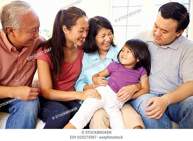 Multi Generation Family Sitting On Sofa At Home Together