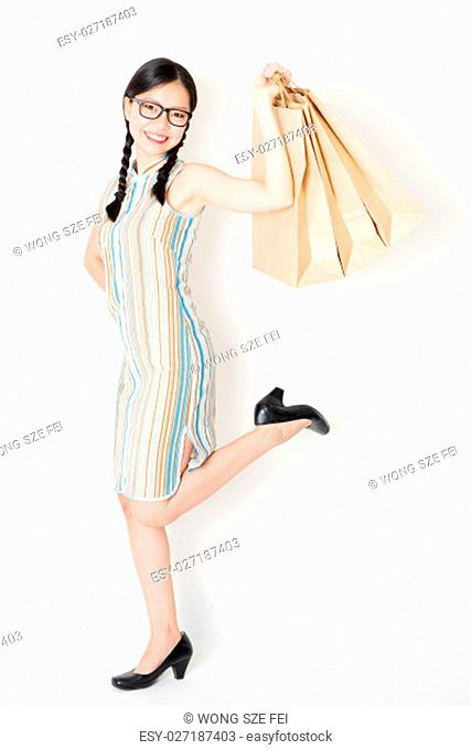 Portrait of young Asian girl in traditional cheongsam dress shopping, hand holding paper bag, celebrating Chinese Lunar New Year or spring festival