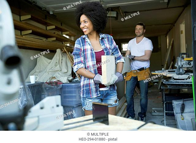 Couple in garage carrying wood plank for home improvement project towards table saw