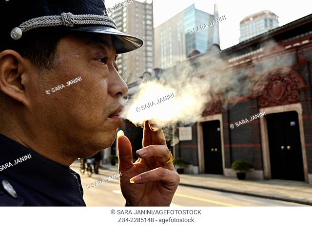 A policeman smoking and behind the building where the Chinese Communist Party was founded in 1921 which now anchors one end of the upscale Xintiandi New Heaven...