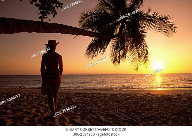 A woman looking at the sunset over the Pacific Ocean at a beach in Costa Rica