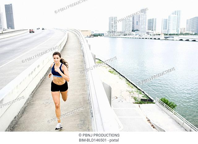 Hispanic woman running near urban waterfront