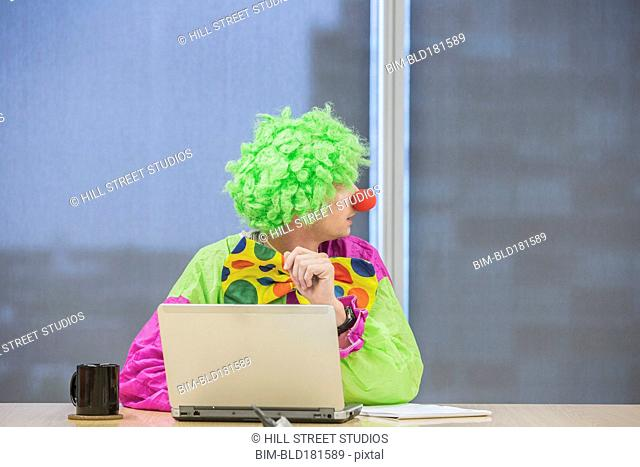 Caucasian businessman wearing clown costume in office