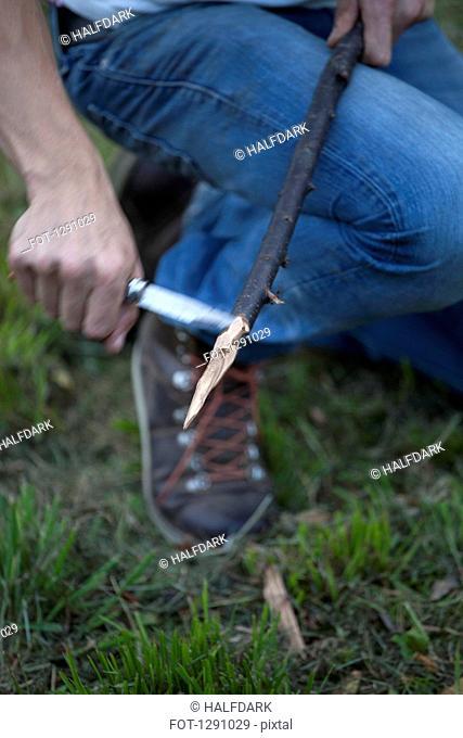 Man cutting stick with knife, close-up