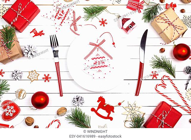 Festive table setting with cutlery and Christmas decorations on white wooden table. Top view. Christmas tableware