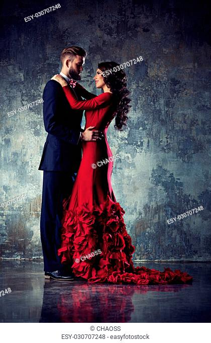 Young elegant loving couple in evening dress portrait. Woman in red and man in black suit embracing