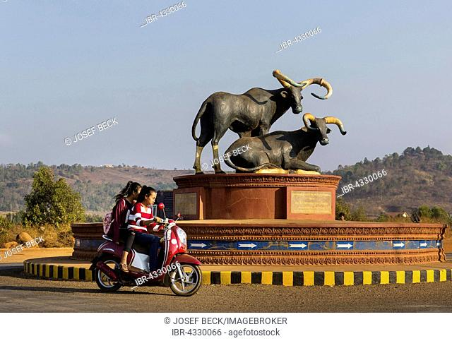 Bull monument at the roundabout, moped with young girls, Senmonorom, Sen Monorom, Mondul Kiri, Mondulkiri Province, Cambodia