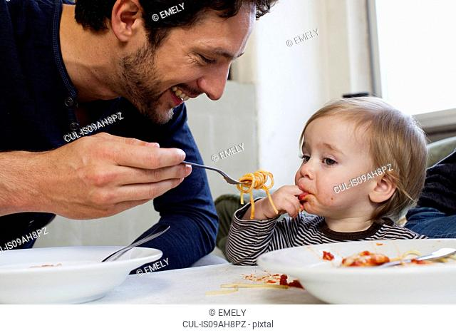 Father feeding one year old daughter spaghetti
