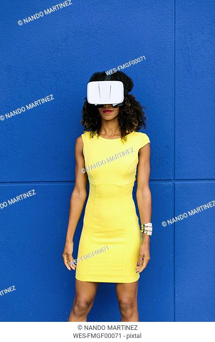 Woman in yellow dress wearing Virtual Reality Glasses against blue background