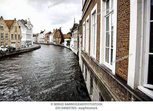 BRUGES, BELGIUM - SEPTEMBER 05, 2018: Canal in Bruges and famous Belfry tower on the background in a beautiful autumn day, Belgium on September 05, 2018