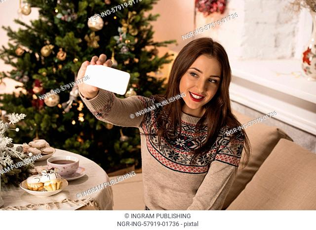 Young pretty woman taking selfie at home while sitting on sofa near Christmas tree