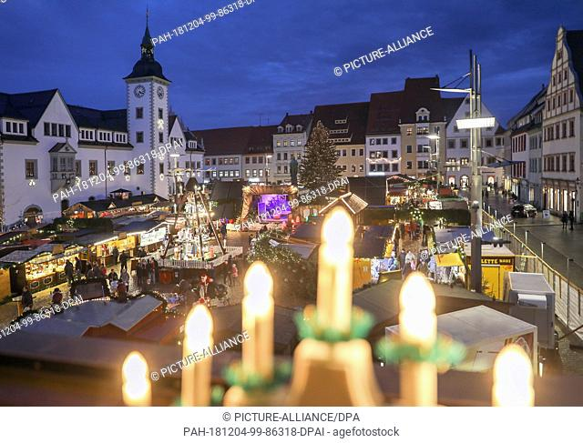 03 December 2018, Saxony, Freiberg: View past a Schwibbogen to the Christmarkt on the Obermarkt. For a total of 27 days, the Christmas market with a strong...