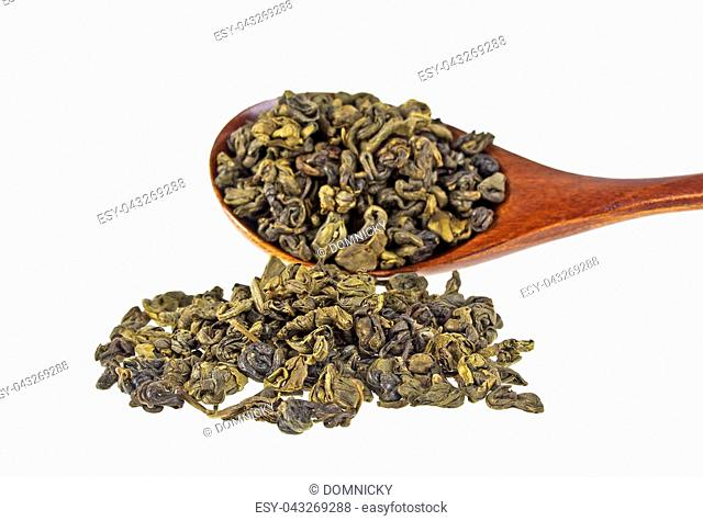 Dry green tea leaves in wooden spoon on white background