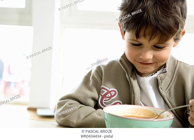 Close-up of a boy looking at a bowl of soup