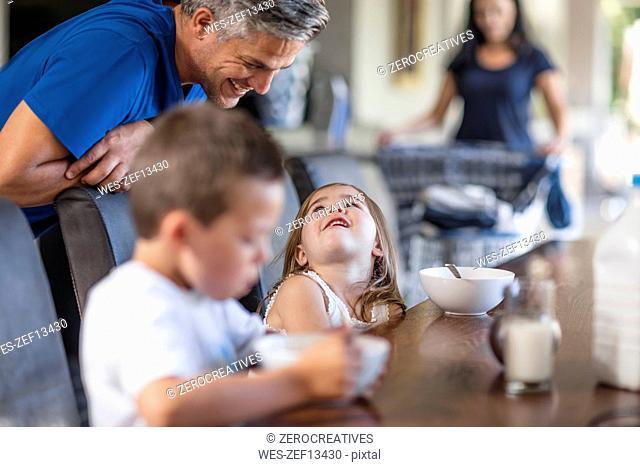 Happy family enjoying breakfast at table