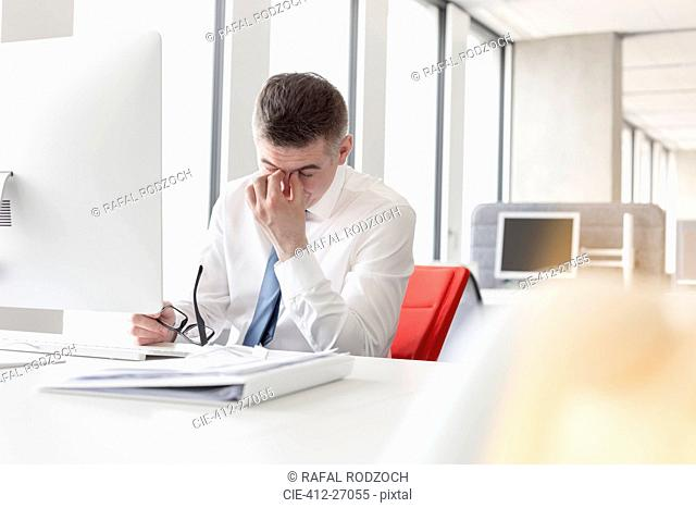 Tired businessman rubbing eyes at computer in office