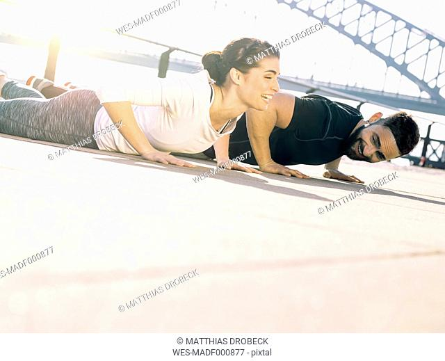 Germany, Cologne, Young couple worming up for workout
